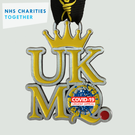A yellow metal medal: UKMQ with a crown